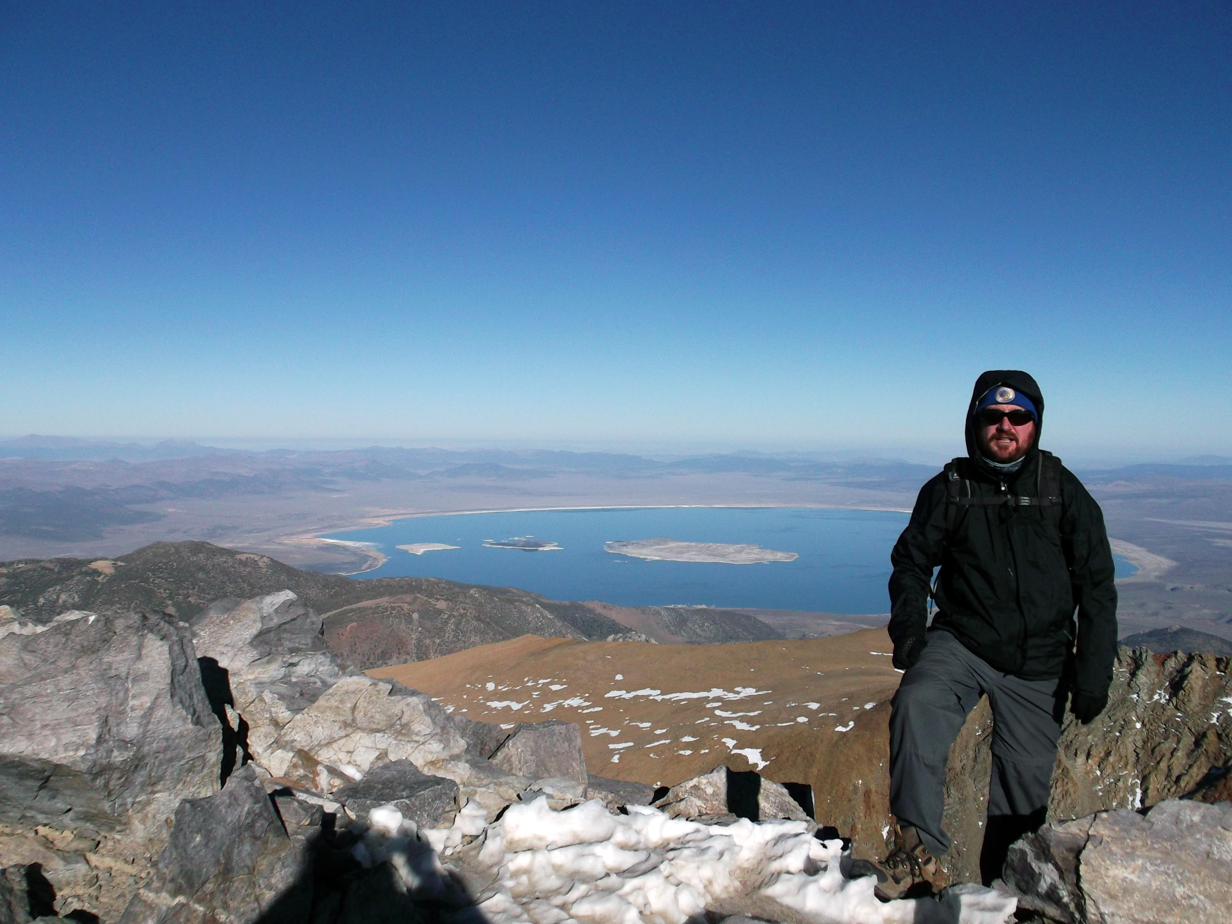 Shane towers over Mono Lake from the summit of Mt. Dana, as the vastitudes of Nevada's Great Basin Desert curve away behind him.  (photo by D. Speredelozzi)