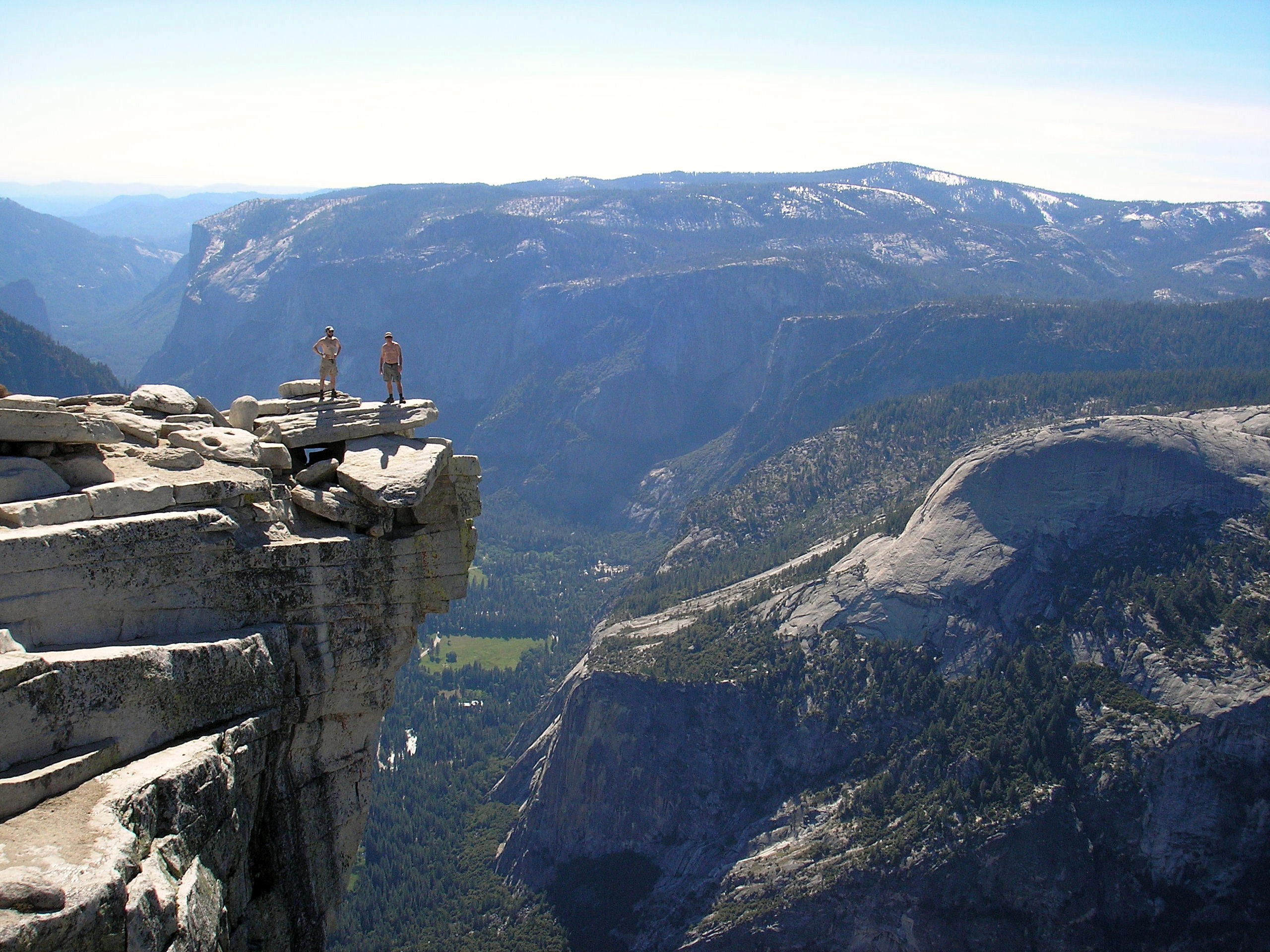 Perched nearly a vertical mile above Yosemite Valley, a pair of fools stands on the summit of Half Dome, one of the world's most recognized and respected granite monoliths.   (photo by John Random)