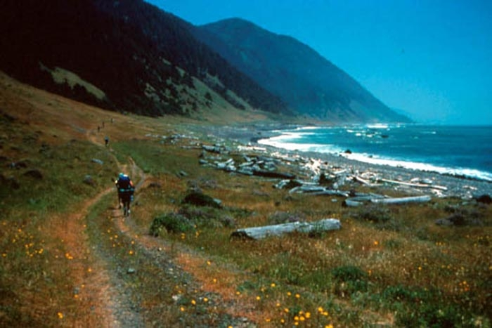 A hiker traverses the long flat bench of Spanish Flat, midway along the route.  (photo by Unknown)