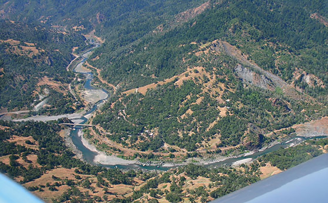 Seen from the air, the Dos Rios Road bridge, at the confluence of the Eel's Main and Middle Forks, and its junction with Highway 162. The railroad can be seen in the foreground, bending around the foot of Holmen Ridge, and winding away southward along the Main Fork, opposite, yet paralleling, the paved highway. (photo property of The Eel River Reporter http://eelriver.org/eel-river-reporter/ )